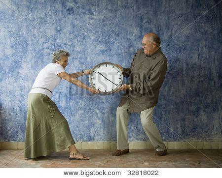 Multi-ethnic senior couple having tug of war with clock
