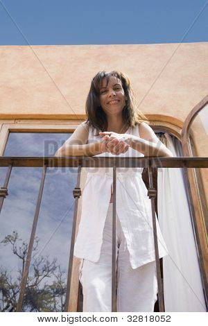 Low angle view of Hispanic woman on balcony