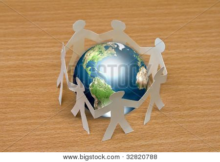 Paper cut of  people standing in a circle around globe on wooden floor  (Elements of this image furnished by NASA)