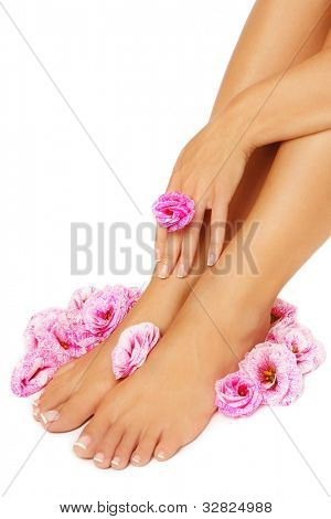 Feet and hand of tanned woman with pink flowers around, on white background