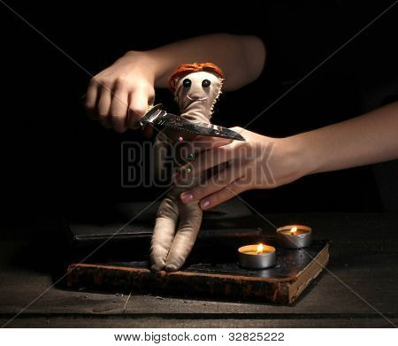Voodoo doll girl pierced by knife on a wooden table in the candlelight