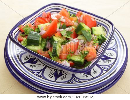 A moroccan salad of tomato, cucumber, onion and coriander (cilantro) leaves tossed in olive oil and vinegar and finished with lemon juice