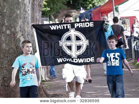 A Man Displaying A White Pride World-wide Flag, Walks Through The Exeter Respect Festival.