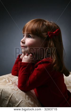 Pretty Girl Kneeling On Couch With Chin On Hands