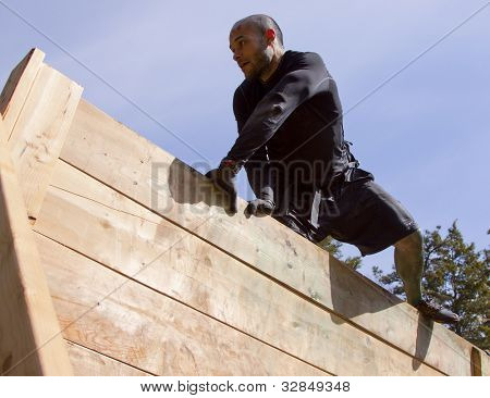 POCONO MANOR, PA - APR 28: A man pulls himself up and over the Berlin Walls obstacle at Tough Mudder on April 28, 2012 in Pocono Manor, PA. The course is designed by British Special Forces.