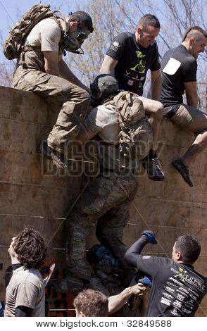POCONO, PA - APR 29: A participant gets help to get up and over the Berlin Walls obstacle at Tough Mudder on April 29, 2012 in Pocono Manor, PA.  The course is designed by British Special Forces.