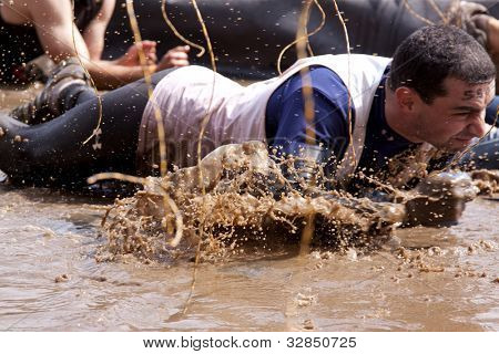 POCONO MANOR, PA - APR 28: A man crawls through water under electrified wires at Tough Mudder event on April 28, 2012 in Pocono Manor, Pennsylvania. The course is designed by British Royal troops.