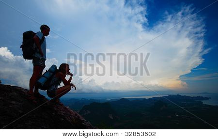 Silhouettes of a young tourists with backpacks relaxing on top of a mountain