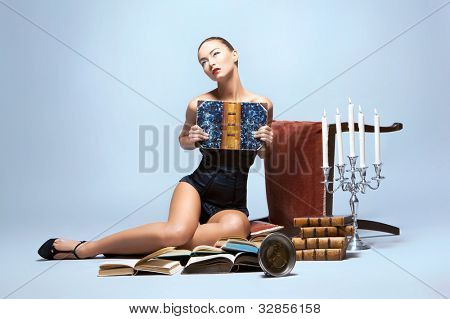Fashion shoot of young sexy woman reading books in nice lingerie