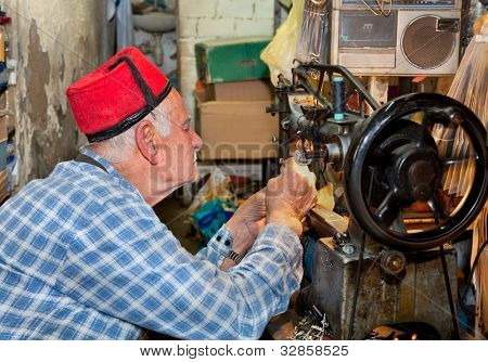 HAIFA,ISRAEL - APRIL 23: Old man with red fezes stitching on tradicional way in Haifa souq on February 23, 2012, Israel.