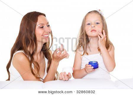 Cute kid applying cream, smiling mom looking at her