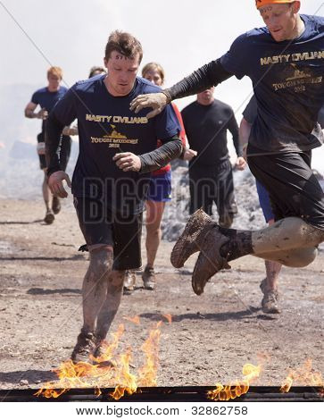 POCONO MANOR, PA - APR 28: A group of men runs through the Fire Walker obstacle at Tough Mudder on April 28, 2012 in Pocono Manor, Pennsylvania. The course is designed by British Royal troops.