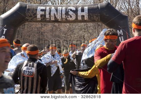 POCONO MANOR, PA - APR 28: Participants use foil wraps to keep warm after the Tough Mudder event on April 28, 2012 in Pocono Manor, Pennsylvania. The course is designed by British Royal troops.