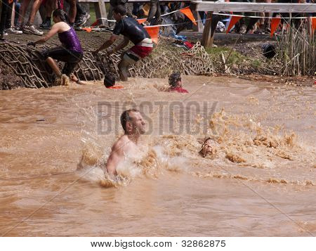 POCONO MANOR, PA - APR 28: A man splashes into water after jumping off an obstacle at Tough Mudder on April 28, 2012 in Pocono Manor, Pennsylvania. The course is designed by British Royal troops.