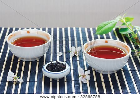 Two cups of tea jar of tea leaves and cherry blossoms with leaves on bamboo table cloth