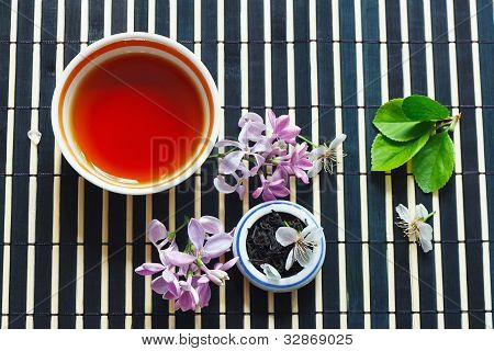 Cup of tea jar of tea leaves and cherry blossoms and leaves with lilac on bamboo table cloth