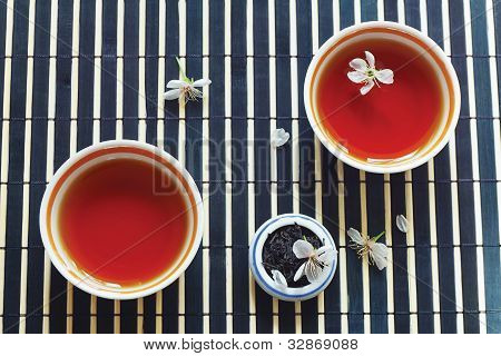 Two cups of tea jar of tea leaves and cherry blossoms on bamboo table cloth