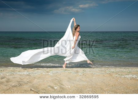 Slim blonde woman runs at the beach, with white shawl