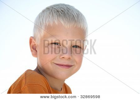 Young blonde kid smiles in orange shirt