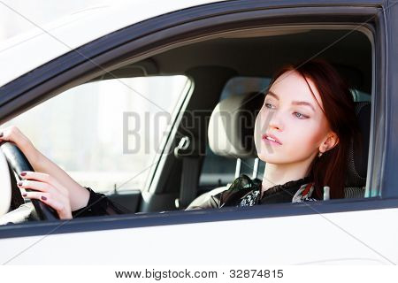 Girl looking in rear view mirror