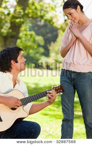 Frau stehend und lächelnd mit den Händen verbunden, wie sie ihr Freund bewundert, die Gitarre spielt