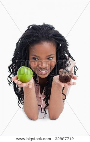 A smiling young woman is holding an apple and a bun on the palms of her hands against a white background