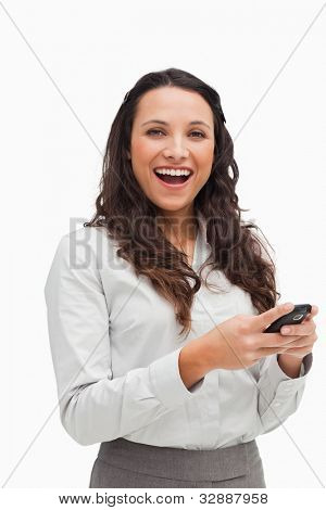 Portrait of a happy brunette looking her text message against white background
