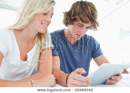 A smiling couple use a tablet together