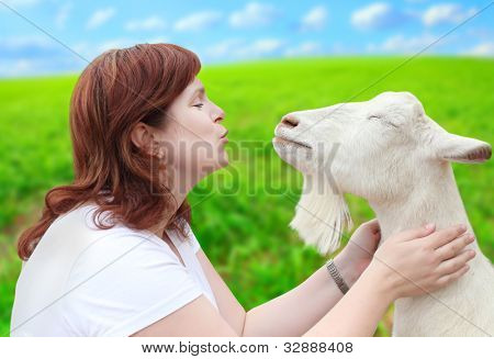 Funny picture of a young farmer woman with his goat.