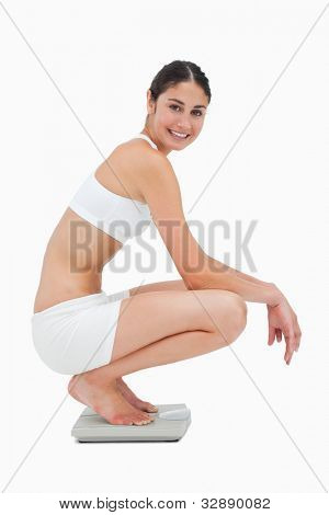 Slim young woman smiling while sitting on a scales against white background
