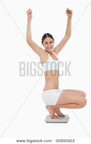 Slim young woman sitting on a scales while raising her arms against white background