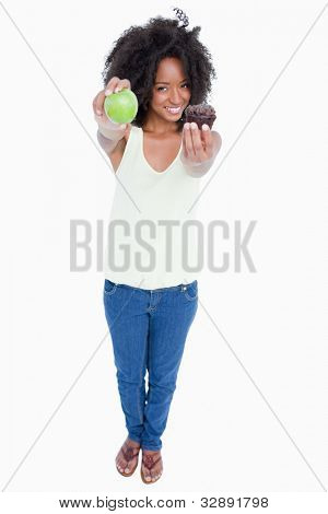 Smiling woman holding an apple in a hand and a muffin in the second one