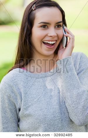 Young woman showing her surprise while talking on the phone and standing in a park