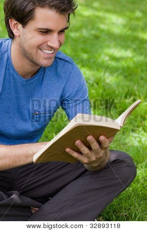 Young smiling man reading a book while siting cross-legged on the grass in a park