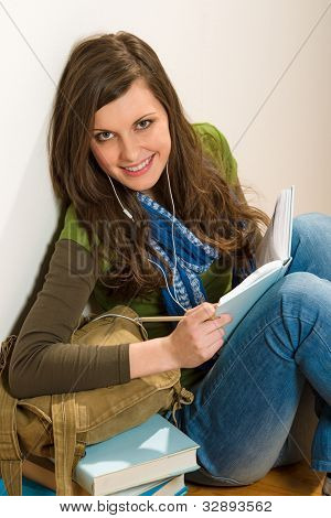 Portrait of student teenager woman with piles of books
