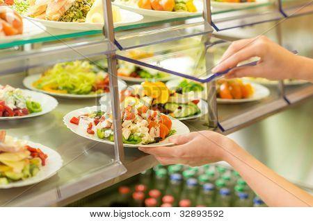 Fresh salad buffet self-service food display human hand take plate