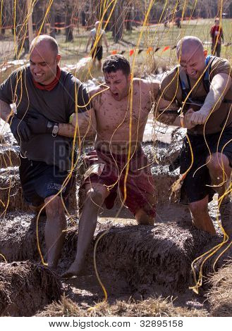 POCONO MANOR, PA - APR 29: A team runs together through obstacle with electrified wires at Tough Mudder on April 29, 2012 in Pocono Manor, Pennsylvania. British Royal troops designed the course.
