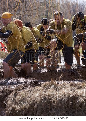POCONO MANOR, PA - APR 29: A team runs through an obstacle with electrified wires at Tough Mudder on April 29, 2012 in Pocono Manor, Pennsylvania. The course is designed by British Royal troops.