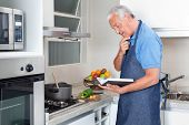 image of saucepan  - Senior man preparing food with the help of recipe book - JPG