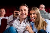Couple and other people, probably friends, in cinema watching a movie, they try to switch to another