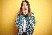 Young beautiful woman wearing casual jacket over yellow isolated background afraid and shocked, surp poster