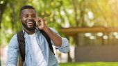 Nice To Hear You. Cheerful African American Guy Having Pleasant Phone Call Outdoors, Panorama With C poster