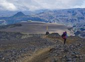 Young Woman Hiker With Backpack At Fimmvorduhals Hiking Trail. Landscape Of Godland With Rugged Gree poster
