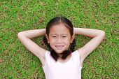 Smiling Little Asian Child Girl With Two Ponytail Hair Lying On Green Grass In The Garden. poster