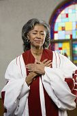 stock photo of piety  - African American female Reverend with hands on heart - JPG