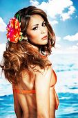 brunette woman in orange bikini with bijou flower in hair, vertical orientation poster