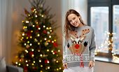 people and holidays concept - happy young woman wearing ugly sweater with reindeer pattern over home poster