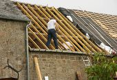 stock photo of gable-roof  - 2 Roof workers restoring ancient tile roof on stone house - JPG