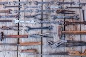 Metal Wrench Rusty Tools Lying On A Black Wooden Table. Hammer, Chisel, Hacksaw, Metal Wrench. Dirty poster