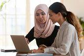 Asian Muslim Female Mentor Teaching Caucasian Intern Explaining Computer Work poster